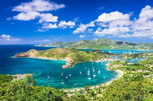sail boats in a cove with sandy beaches and rain forest