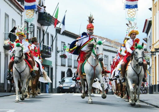 group of men with colorful hats in a parade of azores on horses
