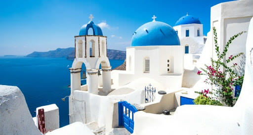 Santorini Greece white homes with ocean view and blue roof tops
